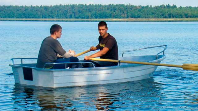 Twee mensen in een polyester roeiboot op het water